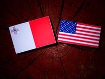 Maltese flag with USA flag on a tree stump. Maltese flag with USA flag on a tree stump Stock Image
