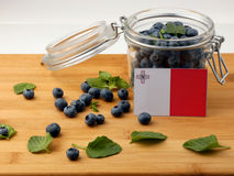 Maltese flag on a wooden plank with blueberries  on whit. E Stock Photos