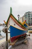 Maltese Luzzu on a boat ramp on shore at Spinola Bay, St. Julian`s, Malta. The bright colors of Luzzu - the traditional Maltese fishing boat pulled up on a boat Royalty Free Stock Image