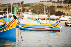 Maltese Luzzu fishing boat, Marsaxlokk, Malta. A view across Marsaxlokk harbor dominated by traditional Maltese fishing boats, Luzzu, decorated in their familiar Royalty Free Stock Images