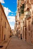 Maltese narrow street in Valetta. With stone buildings in traditional architecture Royalty Free Stock Photos