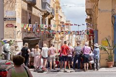 Maltese people fans watch football match on Valletta street. VALLETTA, MALTA - JUNE 24, 2018: Maltese people fans watch football match on Valletta street in Stock Photo
