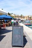 Menu board on the quayside, Marsaxlokk. Maltese sea grill menu board along the waterfront with fishing boats and pavement cafes to the rear, Marsaxlokk, Malta Stock Images