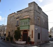 Maltese Tower converted to a Restaurant with traditional balcony Mosta, Malta. This building stands as an island in the main street. The shot shows a fine Royalty Free Stock Image