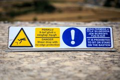 Maltese warning sign. Warning sign in Maltese and English to not sit on the edge for danger of falling off Stock Image