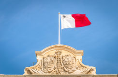 Maltese white and red flag at Malta parliament. Maltese white and red flag against a blue sky - Top of prime minister building parliament in La Valletta capital Stock Photo