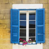 Maltese window decorated with flowers. Building with traditional maltese window decorated with fresh flowers in Valletta Royalty Free Stock Photos