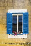 Maltese window decorated with flowers. Building with traditional maltese window decorated with fresh flowers in Valletta Stock Photo