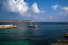 Maltese yacht setting sail. The white yacht sets sail with a beautiful blue sky and azure sea as the back drop Stock Photos