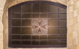 Maltesiskt kors på ett gammalt forntida fönster i fortet St Elmo, Valletta, Malta Inramat av väggar arkivbilder