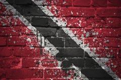 Malująca flaga państowowa Trinidad i Tobago na ściana z cegieł Obrazy Royalty Free