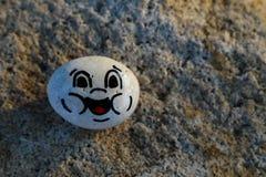 Malujący bielu kamień z szczęśliwą twarzą Fotografia Stock