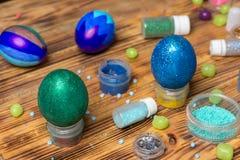 Malujący Easter błyskotliwości jajka, puszki, cukierki na stole, karmowa fotografia Zdjęcie Stock