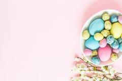 Malujący Easter jajka, kwieciste gałąź, gniazdowy lying on the beach na różowym tle zdjęcie royalty free