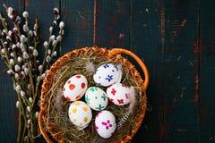 Malujący Wielkanocni jajka w kosza i wierzby gałąź na drewnianym tabl Obrazy Royalty Free
