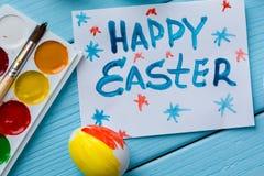 Malujący Wielkanocny jajko, farby, paintbrush i notatka z tytułem pisać farby ` Szczęśliwym Wielkanocnym ` na błękitnym barwionym Zdjęcia Stock