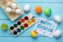 Malujący Wielkanocny jajko, farby, paintbrush i notatka z tytułem pisać farby ` Szczęśliwym Wielkanocnym ` na błękitnym drewniany Obrazy Royalty Free