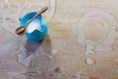 Malutka drewniana łyżka z pojedynczym migdałem balansował przez błękitnego ceramicznego miotacz migdału mleko obraz stock