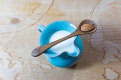 Malutki błękitny ceramiczny miotacz migdału mleko, centrowana, drewniana łyżka z pojedynczym migdałem, balansował nad wierzchołki fotografia stock