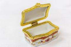 Malutki kolorowy biżuteryjny pudełko z złotem platted crimp w białym tle Makro- z niezwykle płytką głębią pole Fotografia Stock