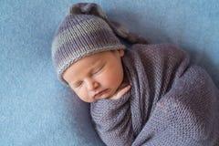 Malutki Sypialny Nowonarodzony dziecko zakrywający z bogatymi purpurami coloured opakunek zdjęcia stock