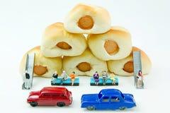 Malutkie zabawki biznesmen i kiełbasa chleb Pojęcia jedzenia tło Fotografia Royalty Free