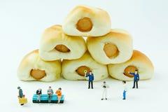 Malutkie zabawki biznesmen i kiełbasa chleb Pojęcia jedzenia tło Obraz Royalty Free