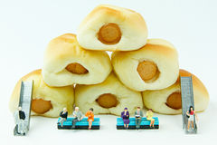 Malutkie zabawki biznesmen i kiełbasa chleb Pojęcia jedzenia tło Zdjęcia Stock