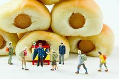 Malutkie zabawki biznesmen i kiełbasa chleb Pojęcia jedzenia tło Zdjęcie Stock
