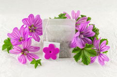 Malva sylvestris, mallow, flowers and teabag. Malva sylvestris, mallow teabag and flowers bouquet on white fabric Royalty Free Stock Images