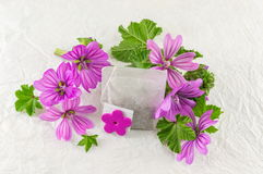 Malva sylvestris, mallow, flowers and teabag. Malva sylvestris, mallow teabag and flowers bouquet on white fabric Royalty Free Stock Photography