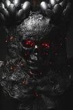 Malvagità, cranio d'argento dell'armatura con l'occhi rossi e luci principali, casco me Immagini Stock