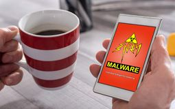 Malware concept on a smartphone. Male hand holding a smartphone with malware concept royalty free stock photo