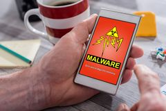 Malware concept on a smartphone. Male hand holding a smartphone with malware concept royalty free stock photos