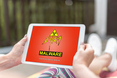 Malware concept on a tablet. Female hands holding a tablet with malware concept royalty free stock image