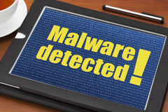 Malware detected alert. On a digital tablet with a cup of tea Royalty Free Stock Photography