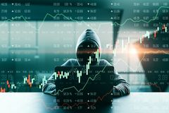 Malware and finance concept. Hacker in hoodie using laptop with glowing forex chart in blurry office interior. Malware and finance concept. Double exposure stock photography