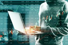 Malware and trade concept. Hacker in hoodie using laptop with glowing forex chart in blurry office interior. Malware and trade concept. Multiexposure stock images
