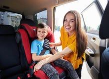 Mamá agraciada que comprueba al hijo que se sienta en asiento del bebé Imagenes de archivo