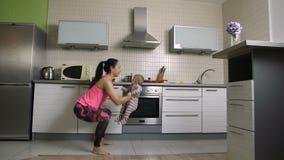 Mamá alegre del ajuste que hace posiciones en cuclillas con el bebé en casa almacen de metraje de vídeo