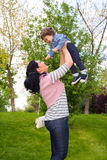 Mamá alegre que cría para arriba al niño Foto de archivo libre de regalías
