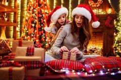 Mamá alegre y su muchacha linda de la hija que intercambian los regalos Padre y pequeños niños que se divierten cerca de árbol de fotos de archivo
