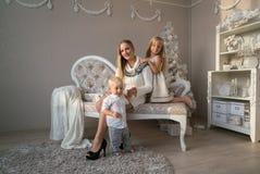 Mamá alegre y sus niños lindos que juegan junto cerca del árbol de navidad dentro Imágenes de archivo libres de regalías
