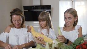 Mamá atractiva y sus hijas que limpian los oídos maduros del maíz de cocina de las hojas en casa La familia feliz está limpiando almacen de video