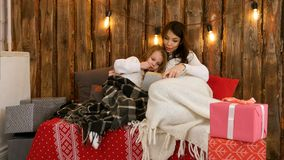 Mamá bastante joven que lee un cuento de la Navidad a su hija linda que se sienta en el sofá envuelto en mantas imagen de archivo