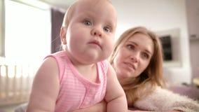 Mamá cansada que detiene al bebé Niño que aprende la colocación Niño hermoso con la madre metrajes