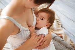 Mamá caucásica joven con el infante en la ubicación interior Bebé del oficio de enfermera de la mamá en un dormitorio blanco Inte imagen de archivo libre de regalías