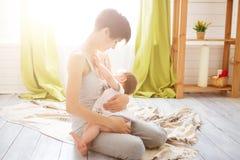 Mamá caucásica joven con el infante en la ubicación interior Bebé del oficio de enfermera de la mamá en un dormitorio blanco Inte fotos de archivo