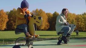 Mamá caucásica y niño rubio en caballo de madera de la calabaza del paseo azul del sombrero almacen de video