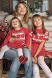 Mamá con dos muchachas en un banco cerca de la casa Foto de archivo